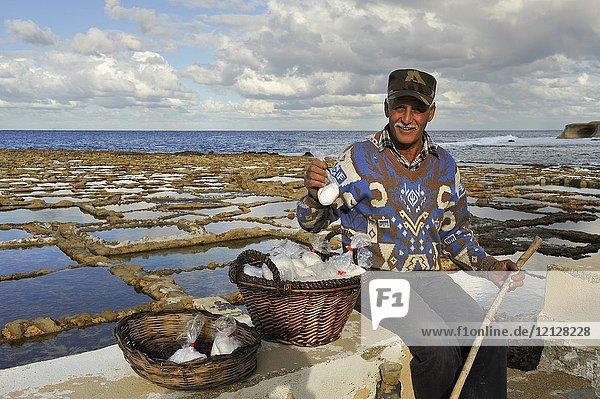 Salt man worker selling salt by the salt pans on the north coast of Gozo Island  Malta  Mediterranean Sea  Southern Europe.