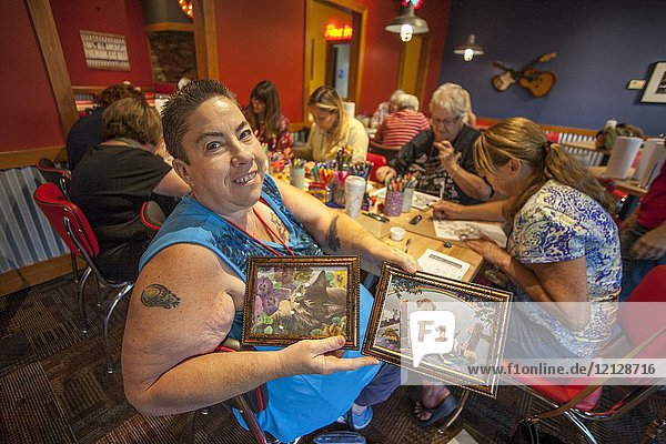 Women of different ages gather at an adult coloring book workshop at a Lake Forest  CA  restaurant function room as a woman proudly shows off her finished work.