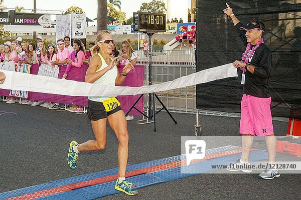 The female winner of a 5K breast cancer fund raising race crosses the ribbon at the finish line in Newport Beach  CA. Note digital timer and number on shorts.