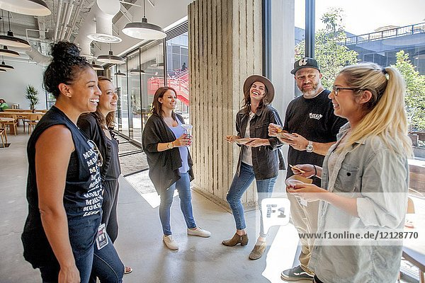 Young adult employees at the Vans Shoe Company corporate headquarters in Costa Mesa  CA  socialize over free snacks. Note central courtyard in background.