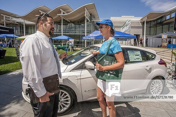 A shopper and a salesman discuss the purchase of an all electric Ford car at an environmental fair in Newport Beach  CA.