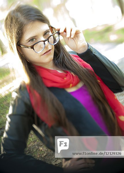 A casual portrait of a 26 year old woman with long brown hair looking over her glasses  outdoors.