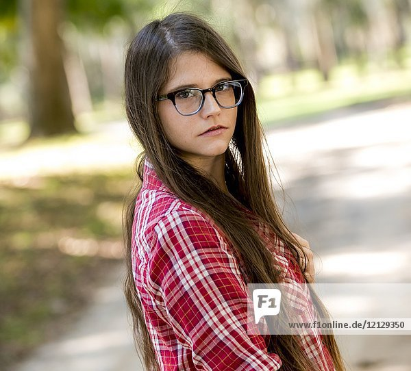 A casual portrait of a 26 year old woman with long brown hair and big glasses looking over her shoulder  on a country road.