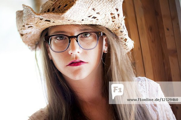 Portrait of a 26 year old woman with messy hair wearing a straw hat and large glasses looking at the camera.