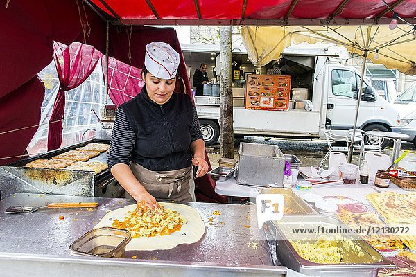Paris  France. Young adult woman preparing baked food at a daily Clignancourt flee market stall. Street-food is usually one of the main attractions of flee-markets  especially when it's made on the spot.