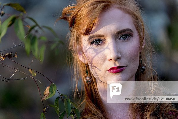 Portrait of a 27 year old redhead woman outdoors.