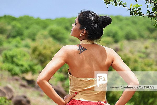 Young woman back profile with tattoo on shoulder.