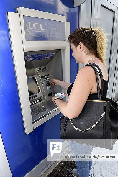 Young woman using an ATM cash machine in Paris  France  Europe.