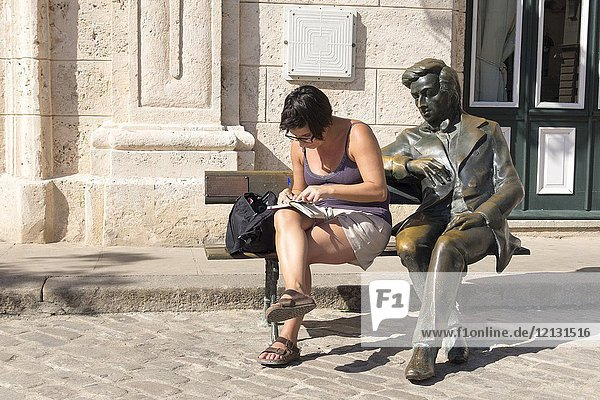 La Habana Vieja district listed as World Heritage by UNESCO  statue of Frederic Chopin sitting. Woman and a bronze statue of man sitting on bench celebrating Frederico Chopin  Havana ( Habana)  Cuba.