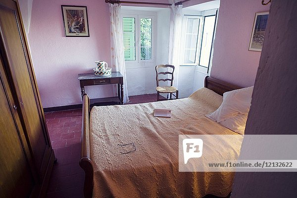 Book and reading glasses on bed in a town house. Santo-Pietro-di-Tenda  Corsica  France