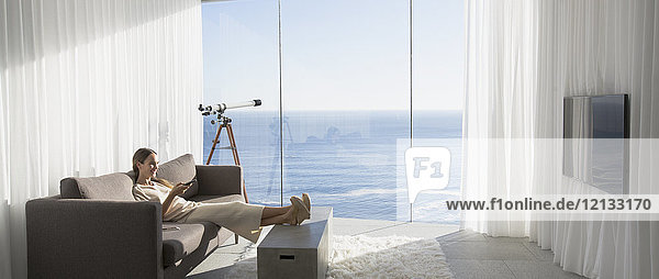 Woman relaxing with feet up  watching TV in modern  luxury home showcase interior living room with sunny ocean view