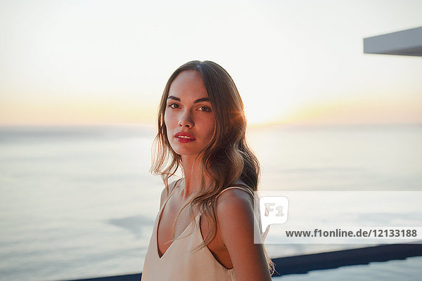 Portrait serious  beautiful woman on luxury patio with sunset ocean view