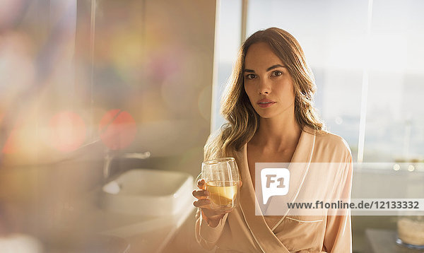 Portrait serious  confident woman in bathrobe drinking water