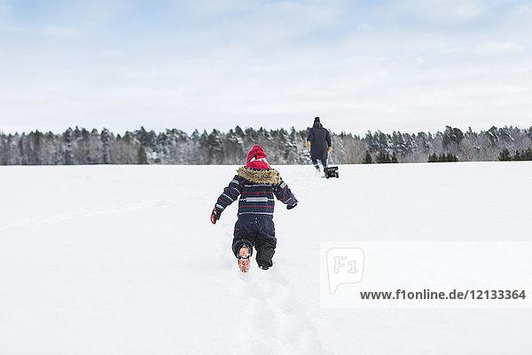 Rückansicht des im Schnee spielenden Kindes