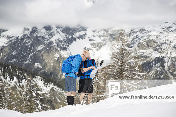 Männer,  die während einer Wanderung auf einen Berg in Courmayeur,  Italien,  eine Karte anschauen