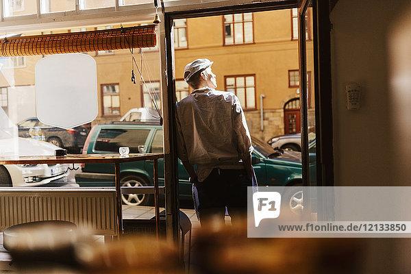 Rückansicht des Metzgers  der sich auf den Eingang des Ladens in Schweden stützt.