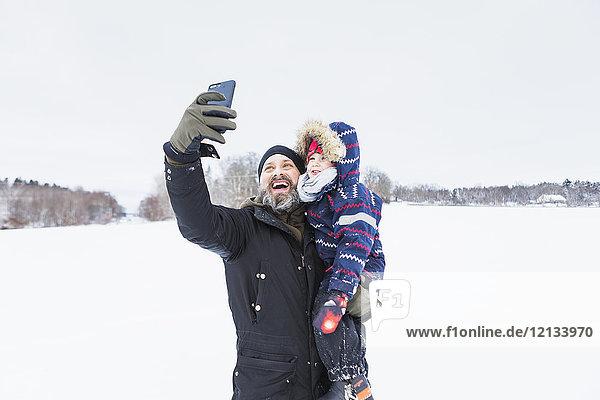 Vater nimmt Selfie mit Sohn im Schnee mit.