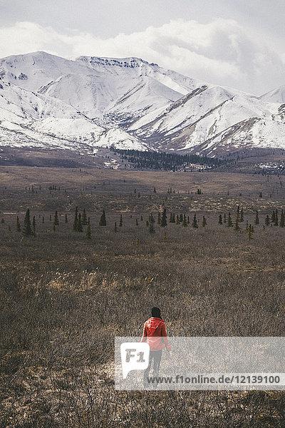 Caucasian woman standing in field near snowy mountain