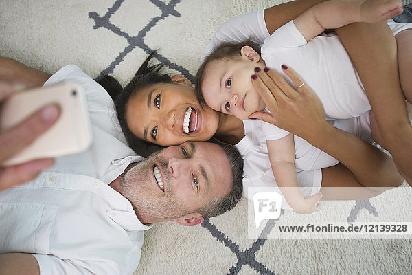 Family laying on floor posing for cell phone selfie