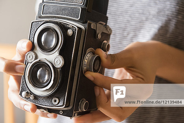 Hands of African American woman using old-fashioned camera