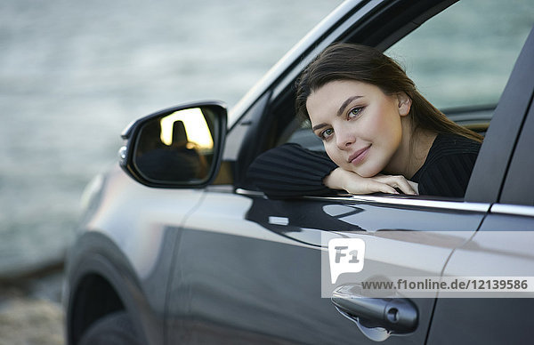 Smiling Caucasian woman leaning in car window