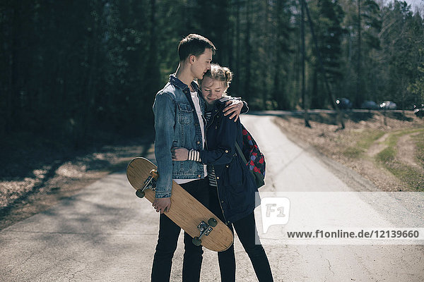 Caucasian couple with skateboard hugging in road