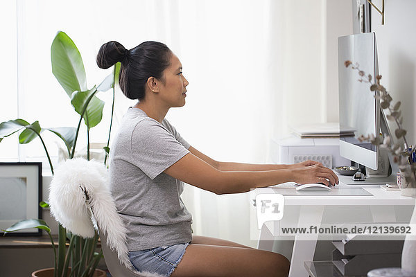 Asian woman using computer in home office