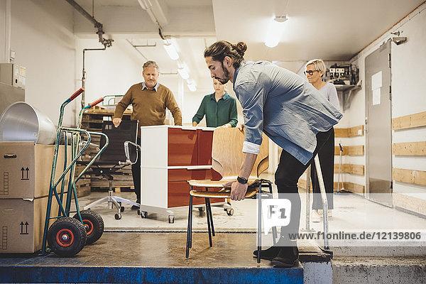 Multiethnische Geschäftsleute mit Geräten  die in ein neues Büro einziehen.