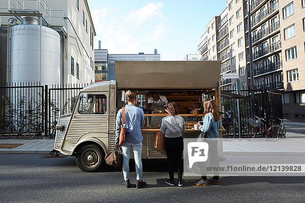 Kunden kaufen Brot vom Verkäufer am Lebensmittelwagen  der in der Stadt geparkt ist.