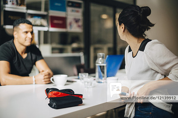 Geschäftsfrau beim Spritzen von Insulin im Gespräch mit Kollegen am Tisch