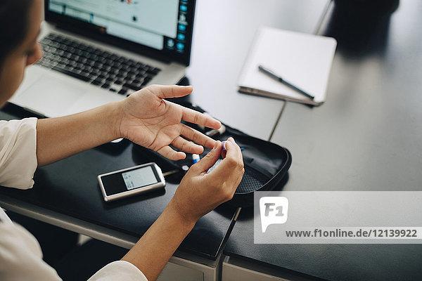 Cropped Geschäftsfrau  die Blutprobe durch Laptop am Schreibtisch im Büro tut