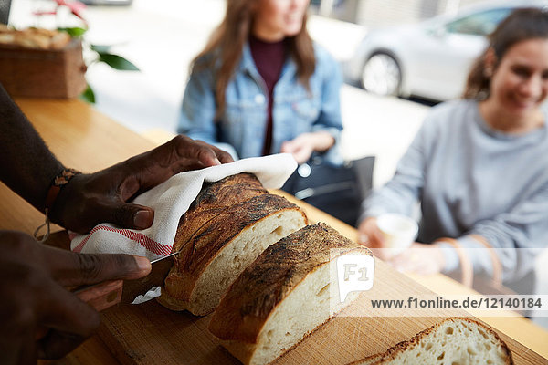 Cropped image of salesman cutting fresh bread for female customers at food truck