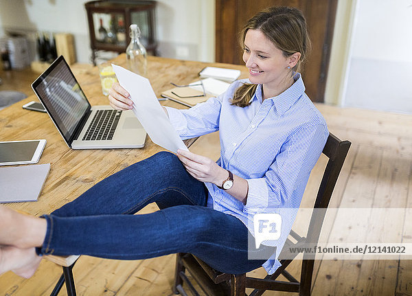 Smiling woman sitting at desk at home with feet up reading document