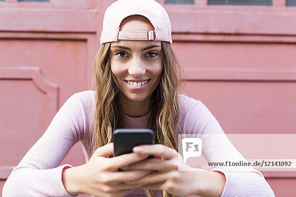 Porträt einer modischen jungen Frau mit Handy in Basecap
