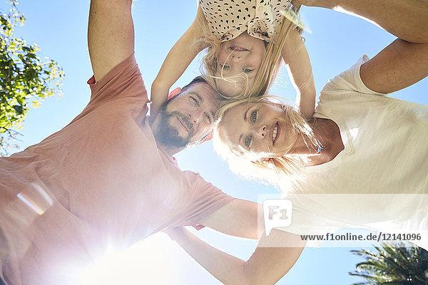 Porträt einer glücklichen Familie unter blauem Himmel
