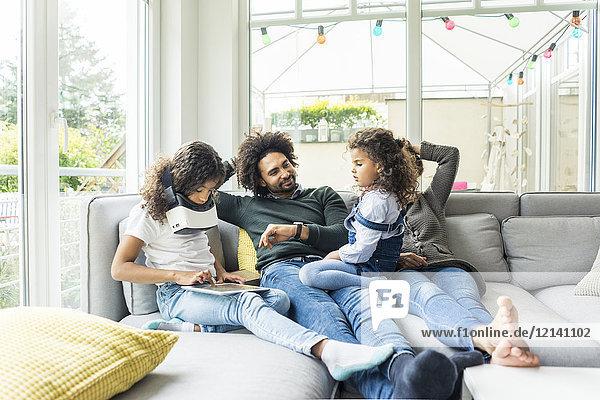 Glückliche Familie sitzt auf der Couch  Tochter spielt mit digitalem Tablett
