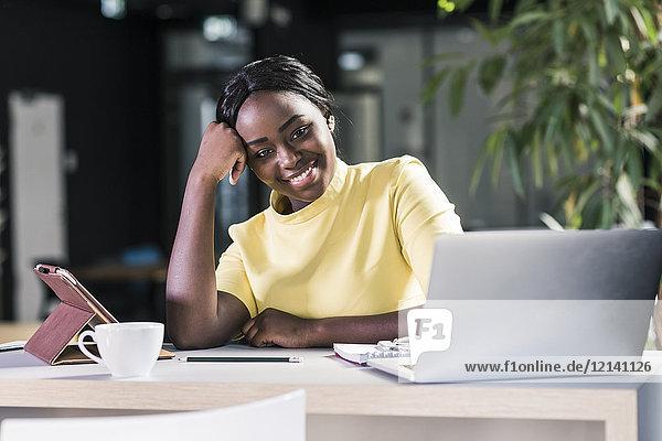Lächelnde Geschäftsfrau mit Laptop und Tablett