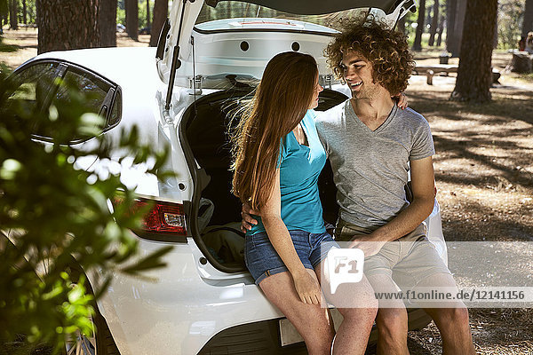 Junges Paar sitzt im Kofferraum eines Autos im Wald