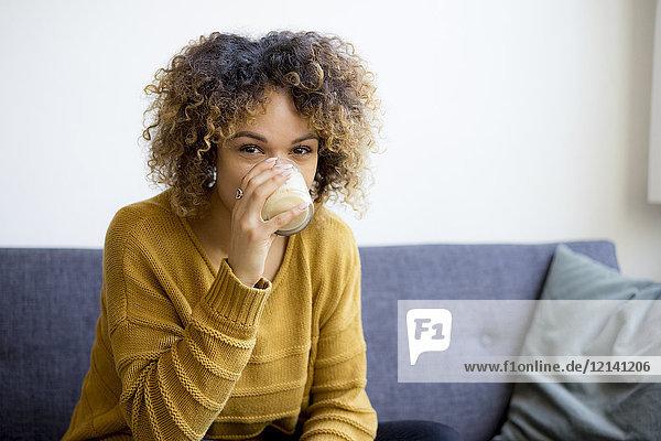 Porträt einer jungen Frau  die zu Hause auf der Couch sitzt und trinkt.