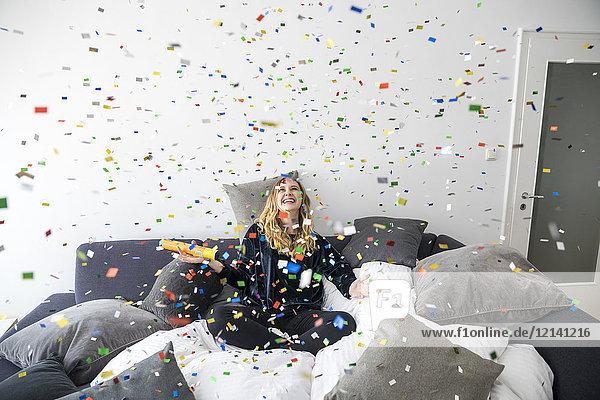 Lachende junge Frau beim Fliegen mit Konfetti zu Hause