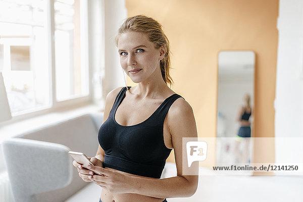 Porträt einer lächelnden jungen Frau in Sportbekleidung mit Handy