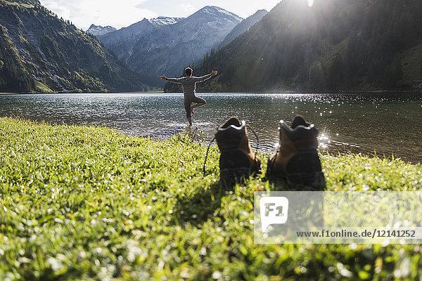 Österreich  Tirol  Wanderschuhe und Mann in Yoga-Pose im Bergsee