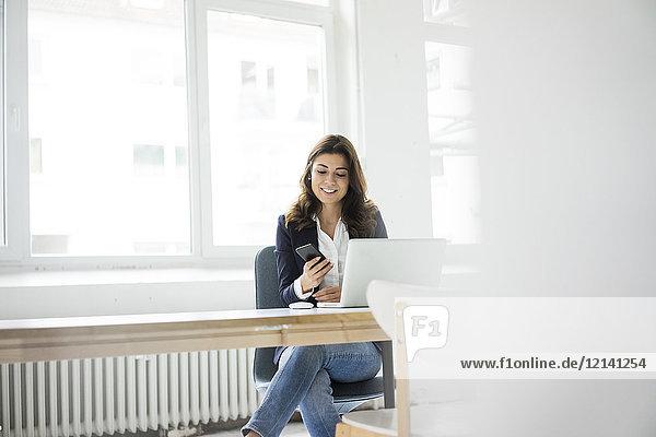 Geschäftsfrau sitzt am Schreibtisch im Büro und arbeitet am Laptop.