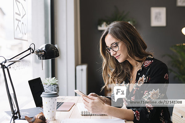 Lächelnde Frau am Schreibtisch im Tattoostudio mit Blick auf das Handy