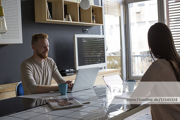 Paar mit zu Hause arbeitenden Laptops