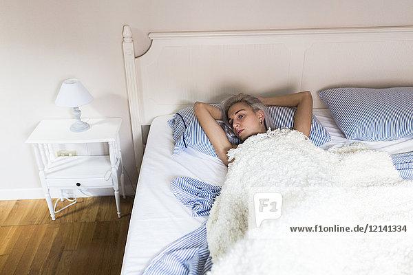 Nachdenkliche junge Frau im Bett liegend