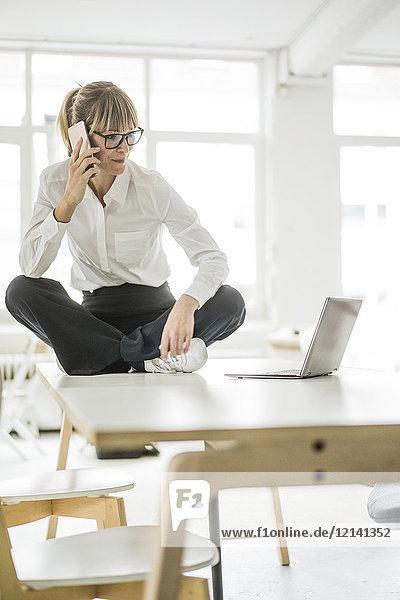 Geschäftsfrau am Schreibtisch im Büro mit Laptop und Handy