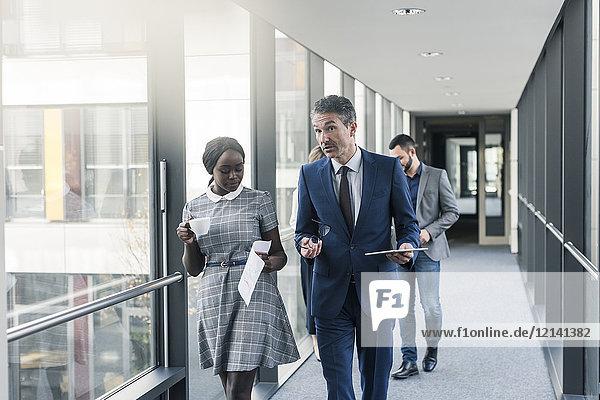 Geschäftsleute  die auf der Büroetage laufen