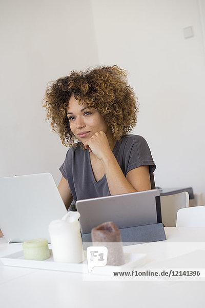 Junge Frau zu Hause mit Laptop und Tablett