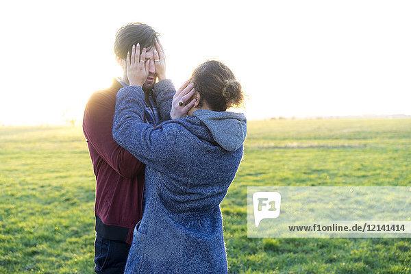 Junges Paar  das auf einer Wiese steht und die Augen bedeckt.